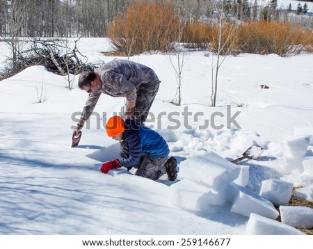 Construction Stages igloo - Eskimo dwelling of ice and snow. Adult and child cut bricks of dense snow - stock photo