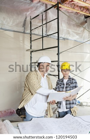 Construction team looking at paper with blueprints on table - stock photo
