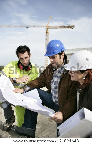 Construction team looking at plans - stock photo