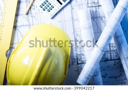 Construction theme, level, ruler, calculator, blueprints rolls, hard hat and pencil - stock photo