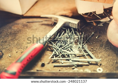 Construction tools, carpentry hammer and nails in work shop. Soft effect on photo - stock photo