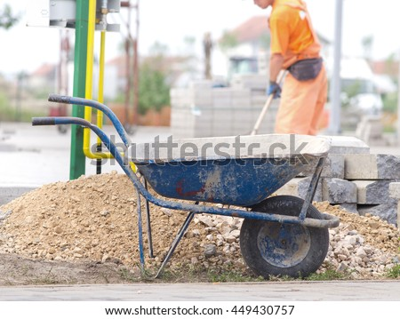 Construction wheelbarrow standing beside gravel and concrete curb stones at building site. Worker in background - stock photo