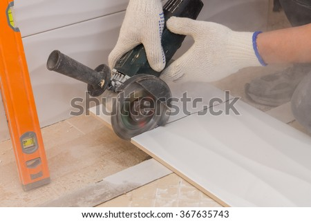construction work laying tile on the wall close up - stock photo
