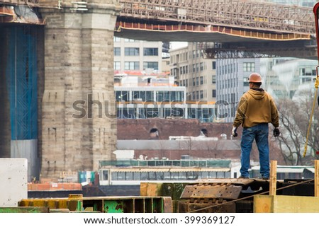 Construction Worker. A man in a hard hat standing in a middle of a construction site. - stock photo