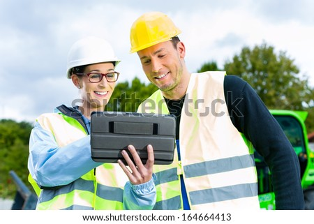 Construction worker and engineer on site discussing blueprints on pad or tablet computer, excavator and other construction machinery in background - stock photo