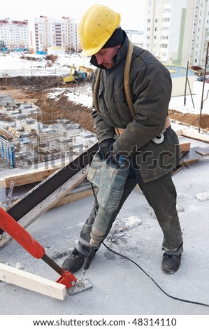 construction worker builder drilling a hole during assembling formwork for concrete filling - stock photo