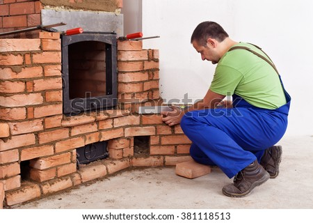 Construction worker building a traditional masonry heater - checking it with a spirit level - stock photo