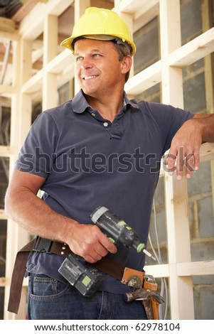 Construction Worker Building Timber Frame In New Home - stock photo