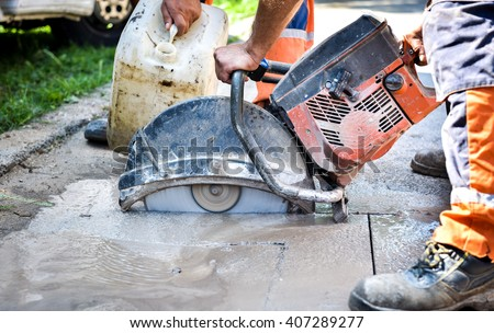 Construction worker cutting Asphalt paving stabs for sidewalk using a cut-off saw. Profile on the blade of an asphalt or concrete cutter with workers shoes and protective gear. - stock photo