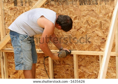 construction worker cutting out window on a new house - stock photo