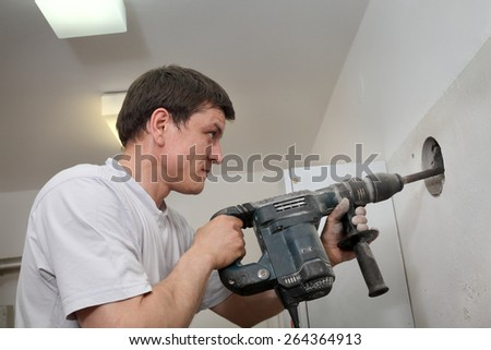 Construction worker demolishing brick wall with electric plugger, chisel hammer tool - stock photo