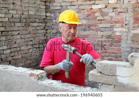 Construction worker demolishing old brick wall with chisel tool and hammer, real people - stock photo