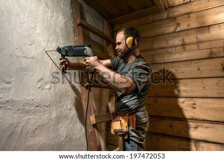 construction worker drill perforate concrete wall on wood background - stock photo