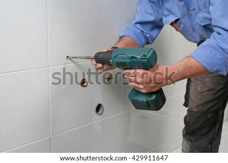 Construction worker drilling holes in the bathroom wall to install a sink. - stock photo