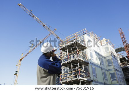 construction worker, giant cranes, scaffolding and building-site in background. early morning shot - stock photo