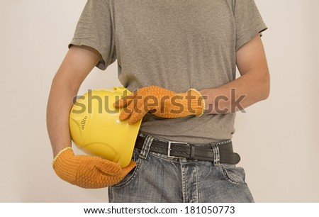 Construction worker hands holding yellow plastic helmet isolated on white background  without gloves keep hard hat close-up  - stock photo