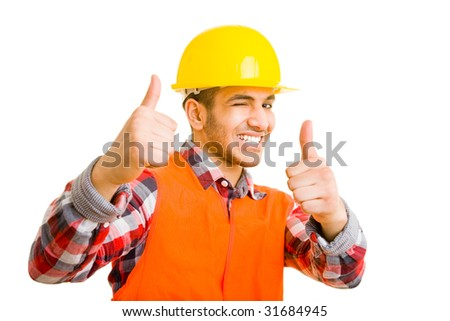 Construction worker holding his thumbs up and winking with his eye - stock photo
