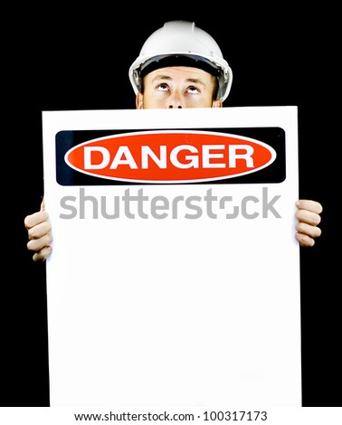 Construction worker in a hardhat holding a blank sign entitled Danger warning of danger from above - stock photo