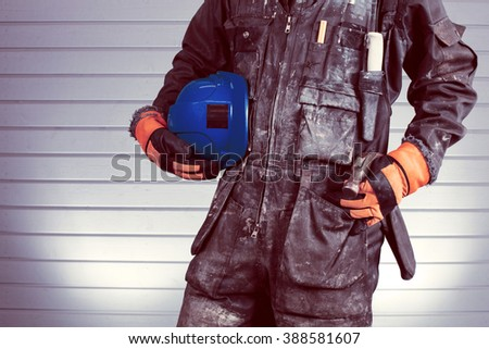 Construction worker in dirty overalls in Finland. The laborer have orange gloves, blue helmet and hammer. Background out of focus and illuminated with flash. Image includes a vintage effect. - stock photo