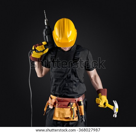 construction worker in helmet with hammer and drill on dark background - stock photo