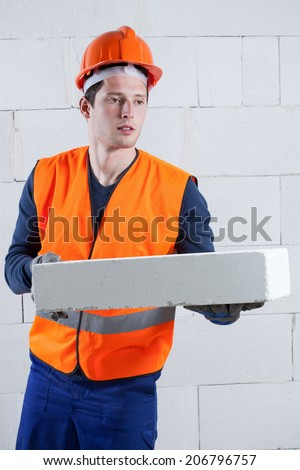 Construction worker in overalls, protective vest and hardhat with a brick - stock photo