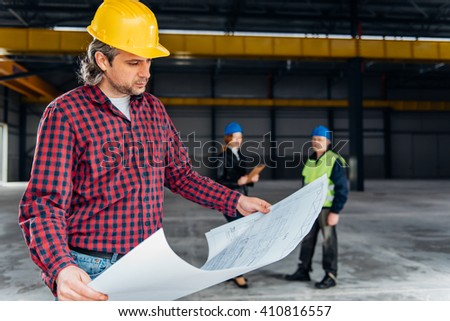 Construction Worker In Safety Helmet reading blueprints - stock photo