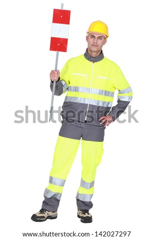 construction worker in safety outfit holding construction sign - stock photo