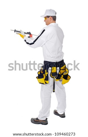 construction worker in white overalls holding a gun silicone sea - stock photo