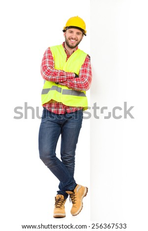 Construction worker in yellow helmet and reflective waistcoat standing leaning on a big white banner. Full length studio shot isolated on white. - stock photo