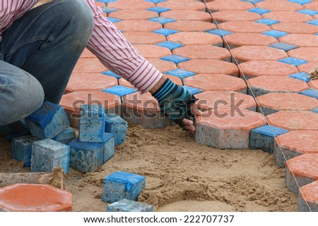Construction worker is installing the brick foot bath, foot bath jigsaw - stock photo