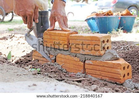 Construction worker laying bricks showing trowel and guideline.  - stock photo