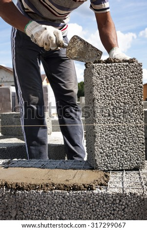 Construction worker laying expanded clay lightweight blocks using cement mortar - stock photo