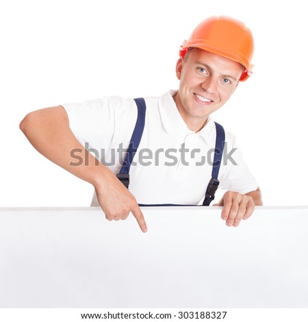 Construction worker leaning over and pointing to blank, isolated on white - stock photo