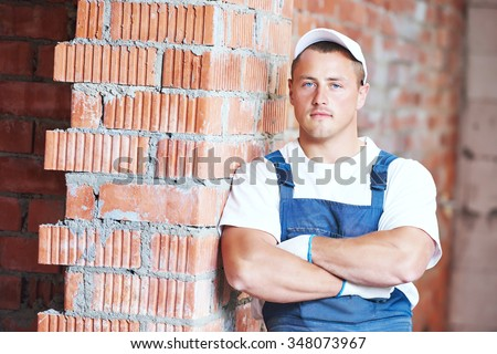 Construction worker. Mason bricklayer standing near brickwall at construction site - stock photo