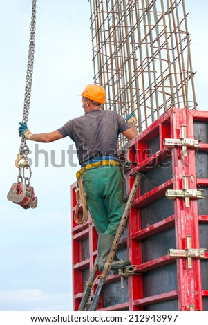Construction worker mounting concrete formwork with crane during house building - stock photo