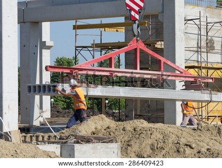 Construction worker navigating with concrete slab lifted by crane at building site - stock photo