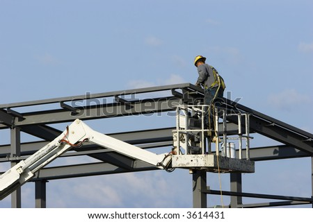 Construction worker on a cherry picker crane erecting a building at a site. - stock photo
