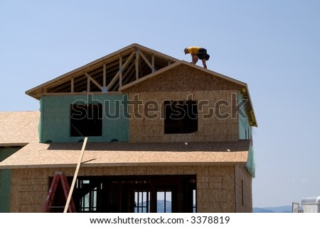 Construction worker  on roof of a new home with mountains in the background - stock photo