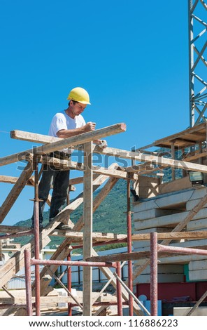 Construction worker on scaffold busy with guiding strings - stock photo