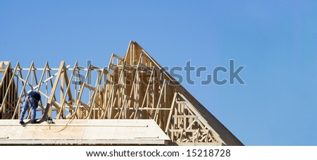 Construction worker on the roof building a house - stock photo