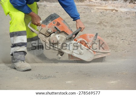 Construction worker operated Circular saw with a diamond blade for cutting asphalt and concrete. - stock photo