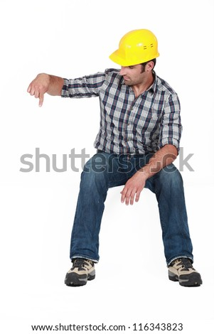 Construction worker pointing down - stock photo