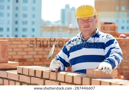 construction worker. Portrait of mason bricklayer installing red brick with trowel putty knife outdoors - stock photo