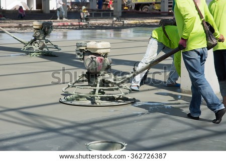 Construction worker produces the grout and finish wet concrete with a special tool. Float blades. For smoothing and polishing concrete, concrete floors - stock photo