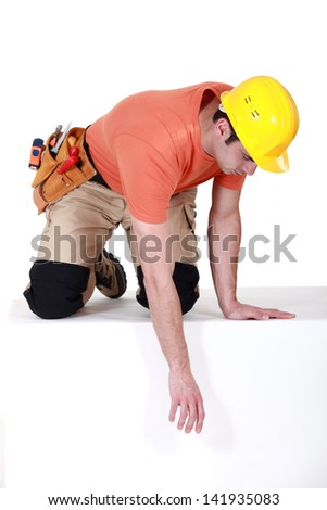 Construction worker reaching down - stock photo