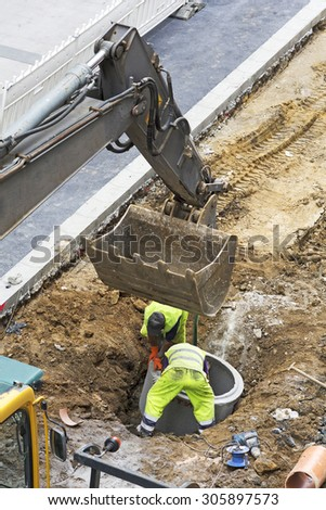 construction worker  repairing the sewer and water  pipes in the street city  - stock photo