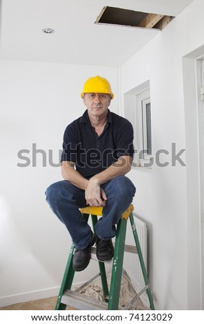 construction worker sat on a ladder inside a house trying to fix a hole in the ceiling - stock photo