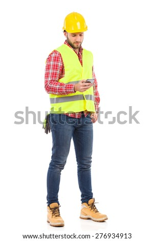 Construction Worker Sending a Text Message. Manual worker in yellow helmet and lime waistcoat using a smart phone. Full length studio shot isolated on white. - stock photo