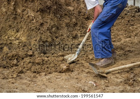 Construction worker shoveling dirt,  shoveling ground. Worker with shovel. Selective focus.  - stock photo