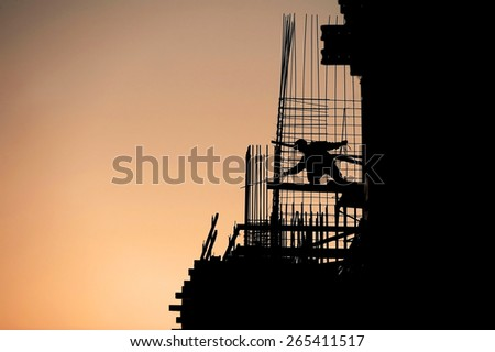 Construction worker silhouette on a construction site at sunset - stock photo